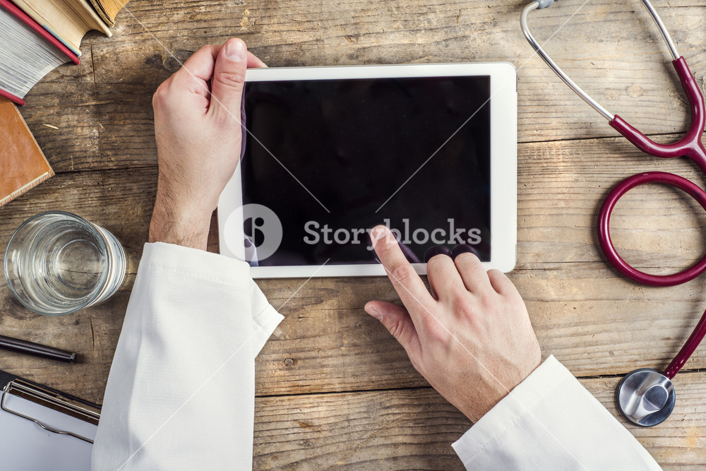 Hands of unrecognizable doctor writing on a tablet. Wooden desk background.