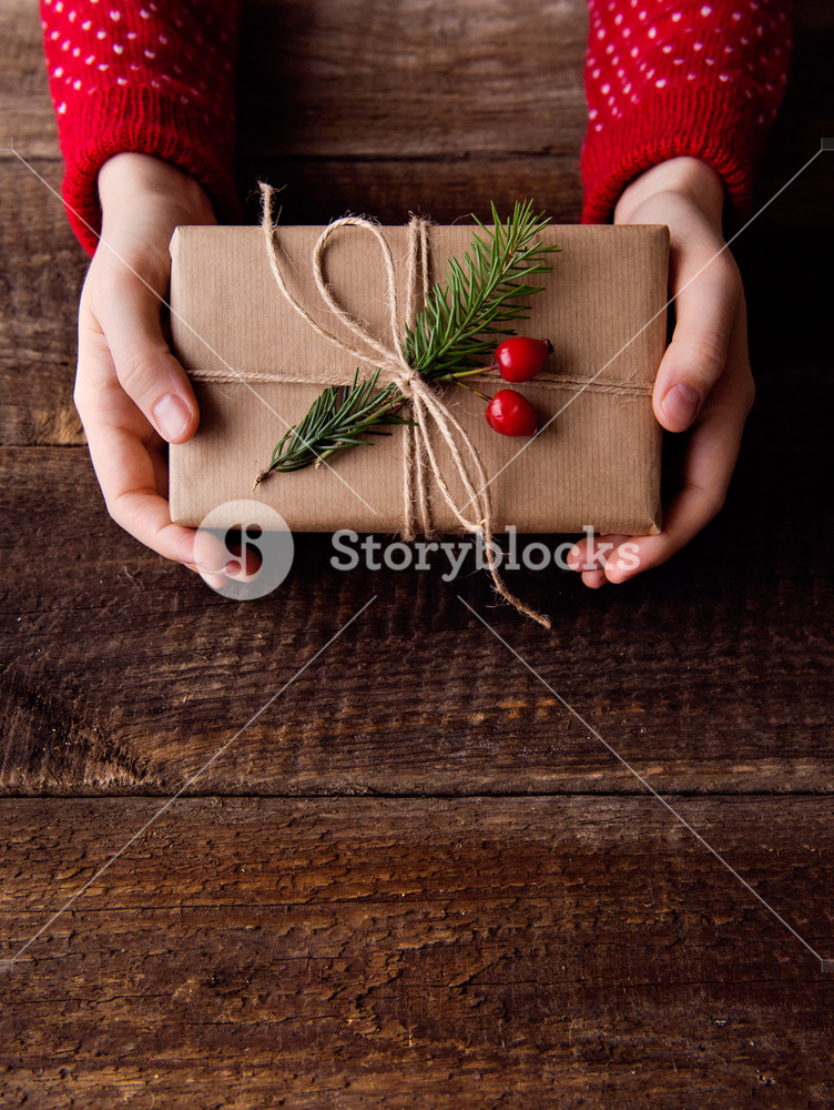 Hands of unrecognizable woman holding wrapped and decorated Christmas present against wooden table background. Studio shot. Copy space.