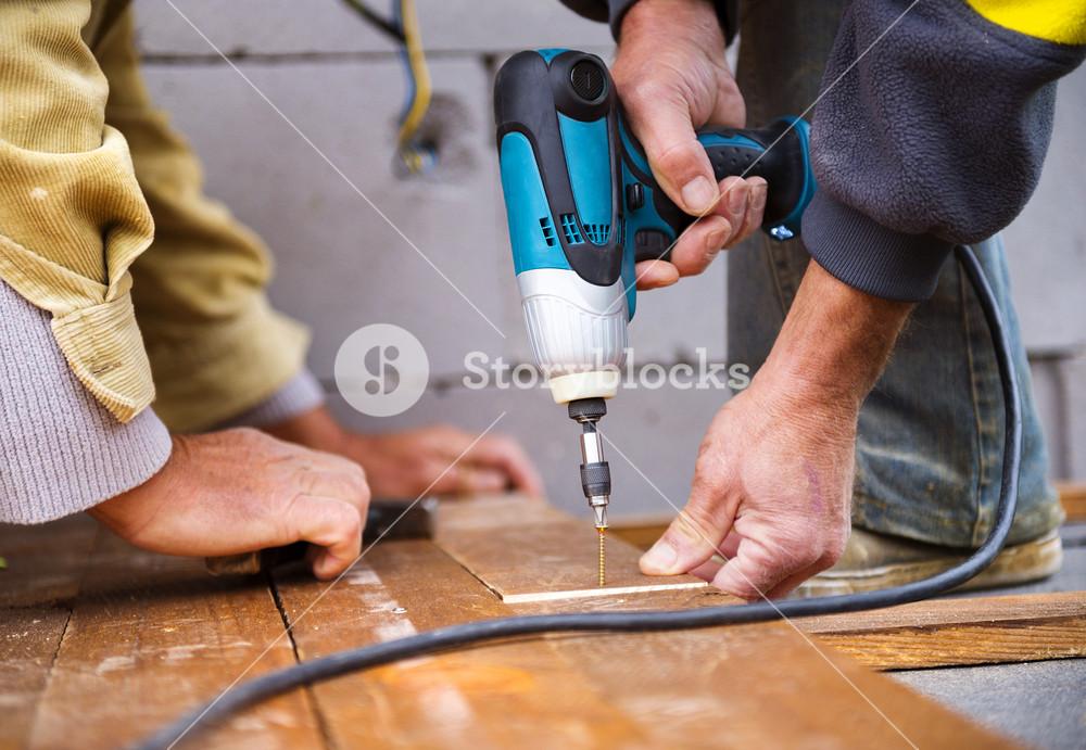 Handymen installing wooden flooring in patio, working with drilling machine