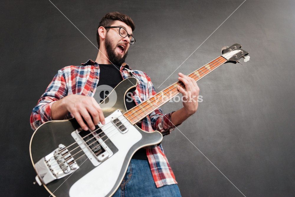 Happy bearded young man in plaid shirt playing guitar and singing over grey background