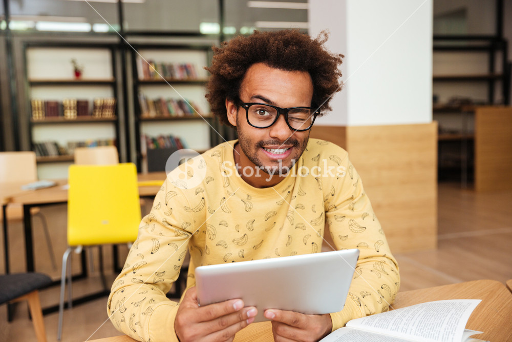 Happy cute african young man in glasses with tablet in library