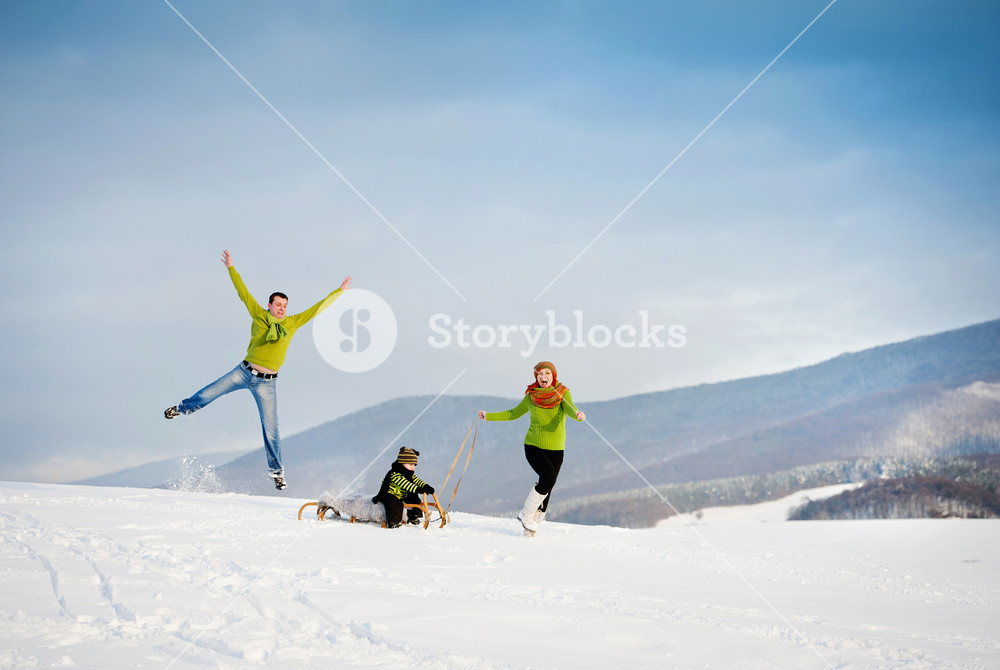 Happy parents with their son riding on sledge having fun outside in the snow.