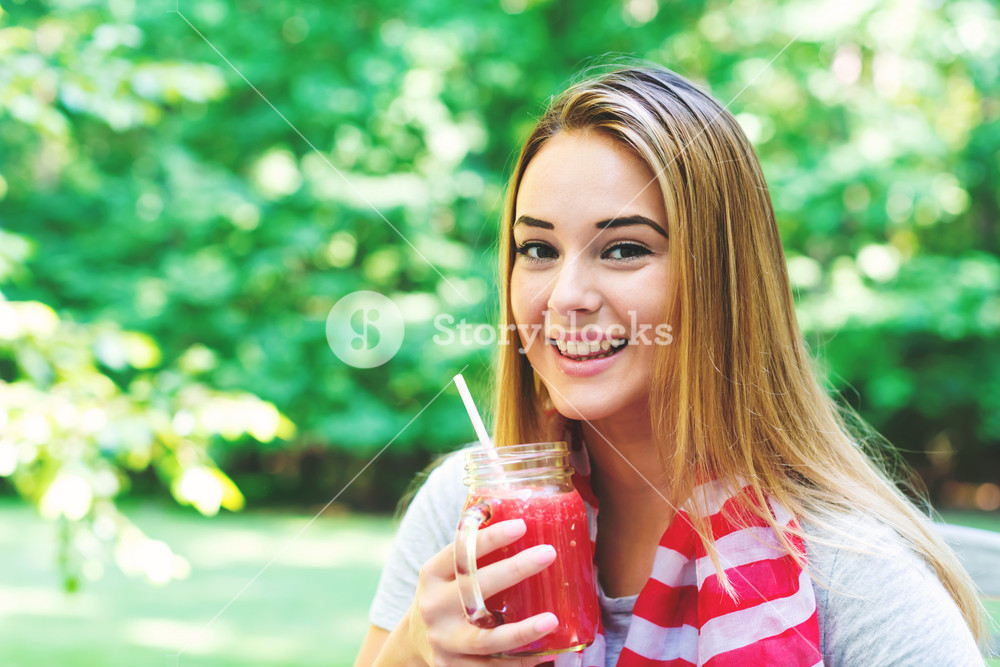 Happy woman drinking a smoothie outside on Independance Day