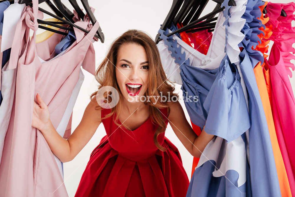 Happy woman shopper in red dress peeking out through clothing in clothes rack isolated on a white background