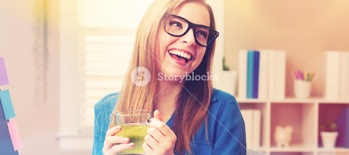 Happy young woman drinking green tea in her home office