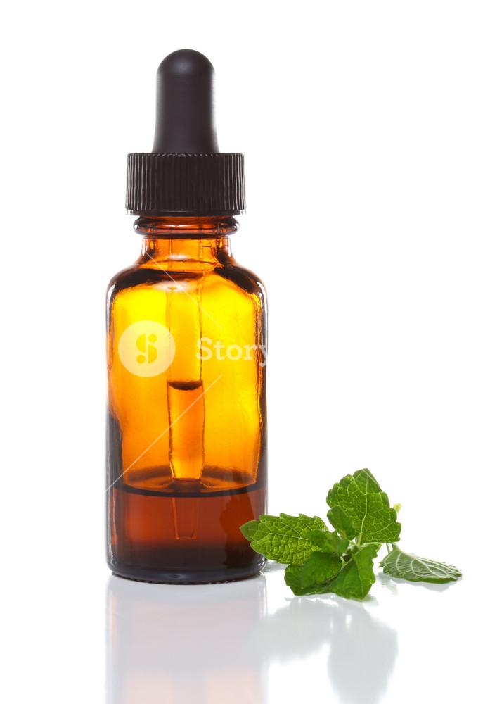 Herbal medicine dropper bottle with mint leaves