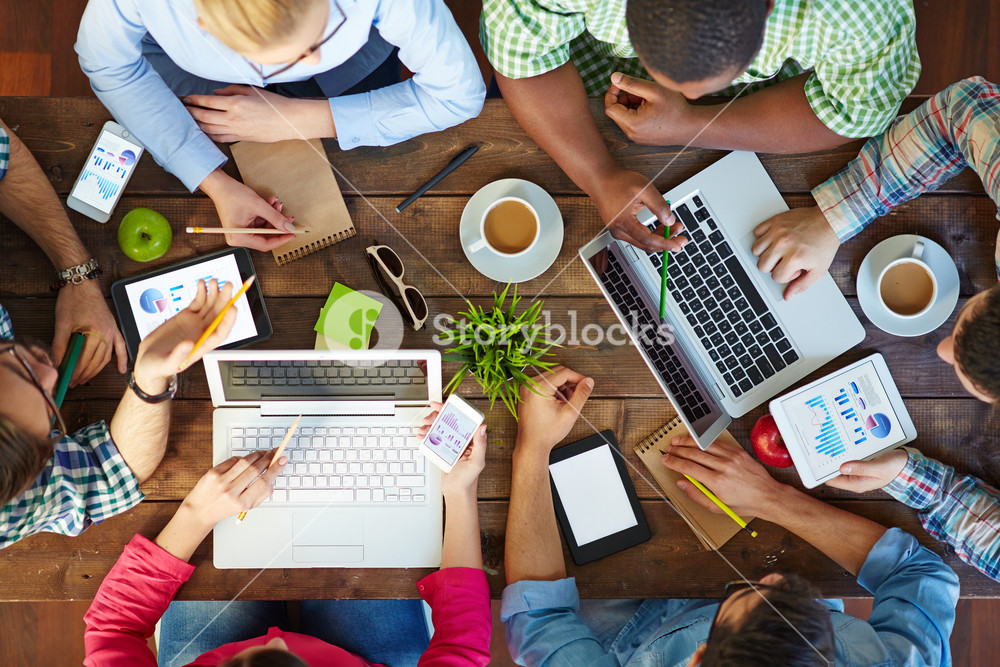 High angle view of people communicating at table with their devices