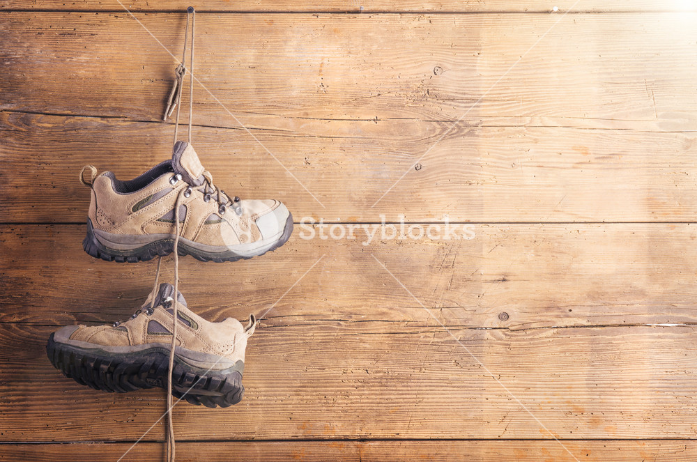 Hiking shoes hang on a wooden fence background