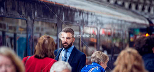 Hipster businessman walking at the station, crowded underground platform, train