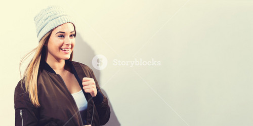 Hipster girl wearing jacket and knit hat on a white background