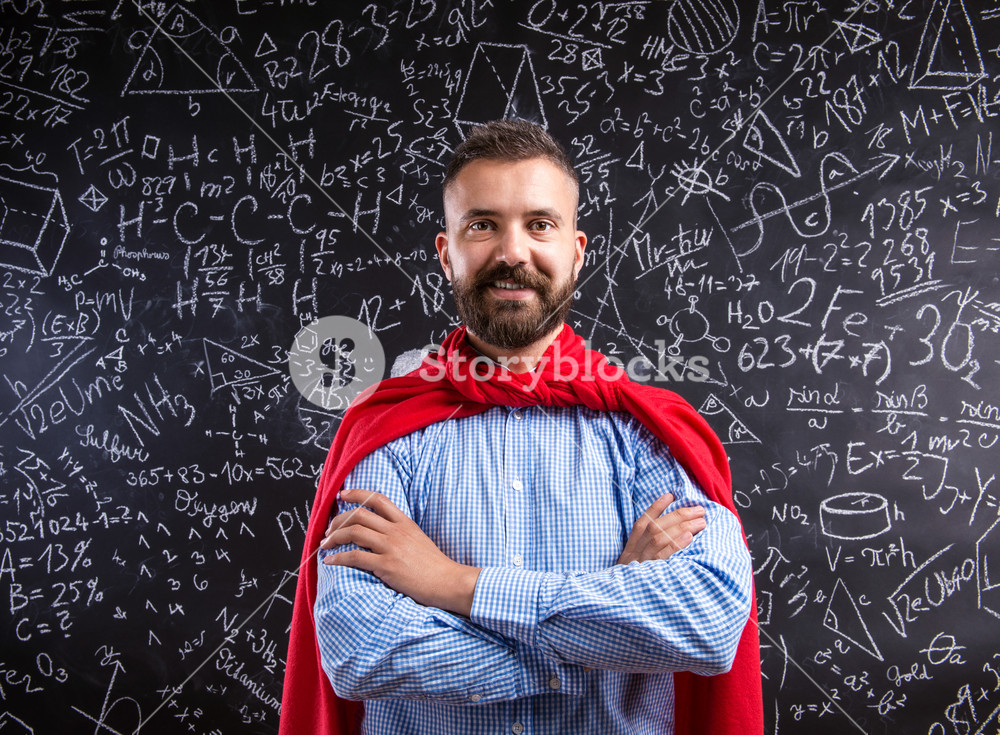 Hipster teacher in red cape standing against big blackboard with mathematical symbols and formulas. Studio shot on black background.