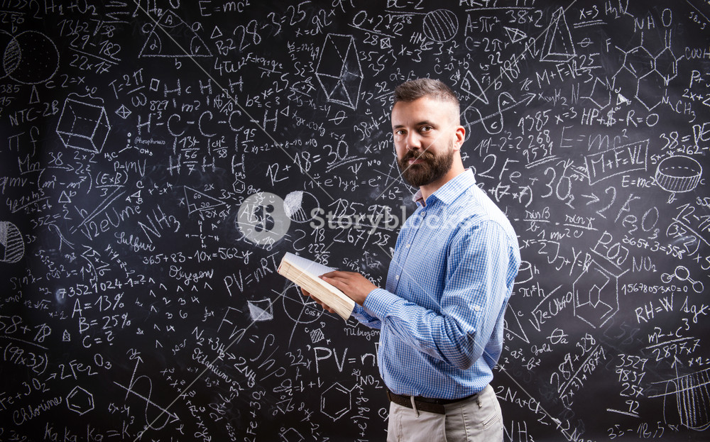 Hipster teacher with book against big blackboard with mathematical symbols and formulas. Studio shot on black background.