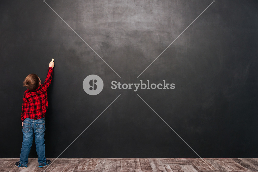 Image of a little pretty child standing near blackboard and drawing on it.