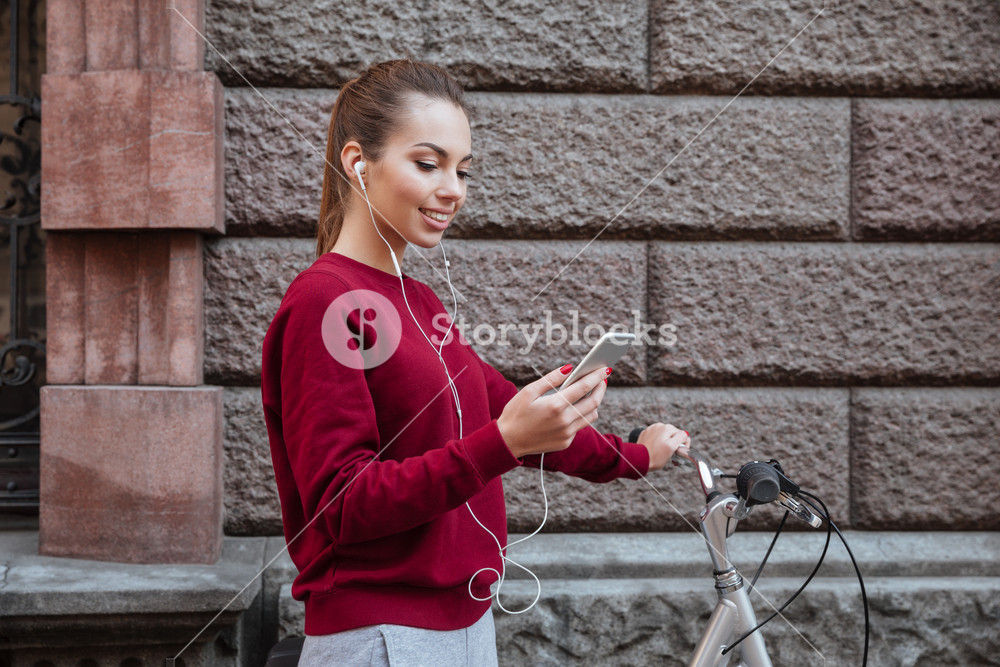 Image of cheerful woman walking with her bicycle in the city while standing near wall and listen to music by her phone. Look at phone.