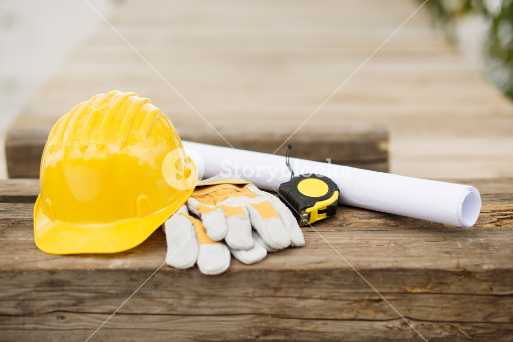 Image of engineer workplace with blueprint, hardhat and measuring tools