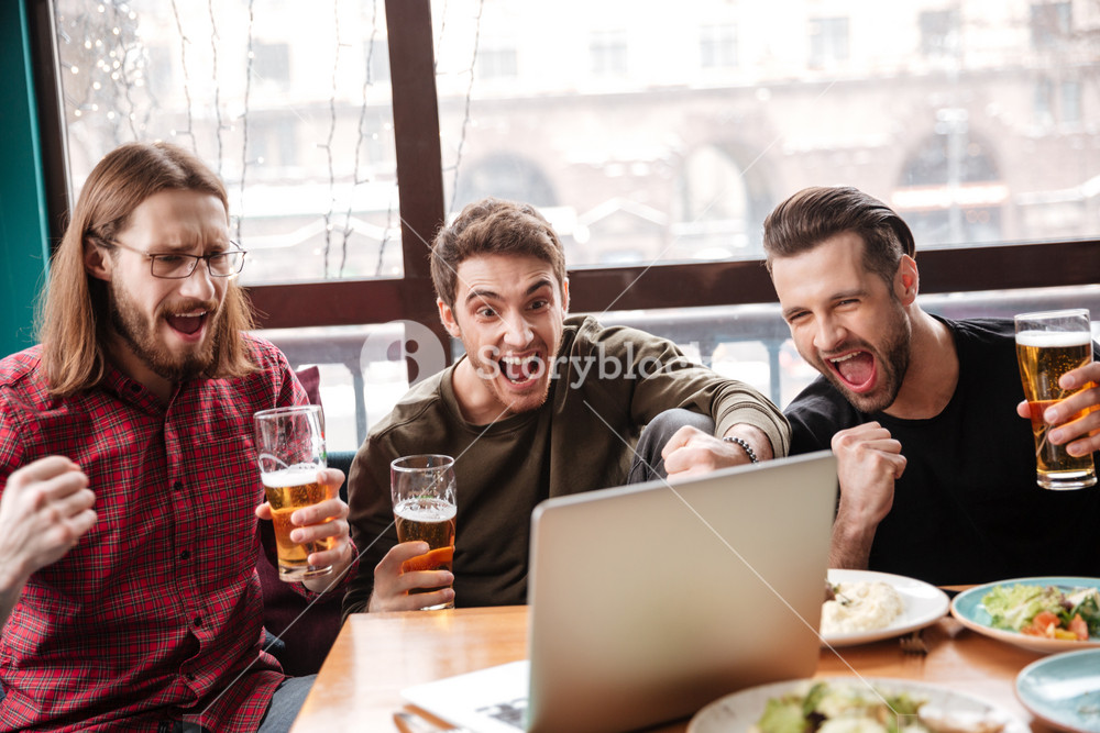 Image of happy men friends sitting in cafe while eating and drinking beer. Using laptop.