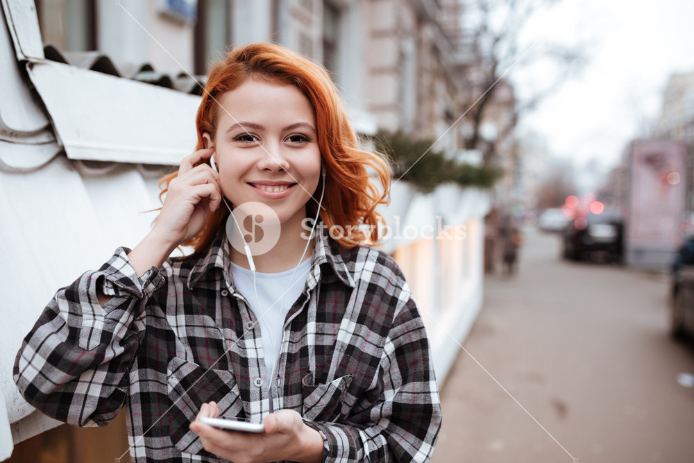 Image of happy young woman with red hair walking outdoors. Look at camera while listen to music and holding phone in hands.