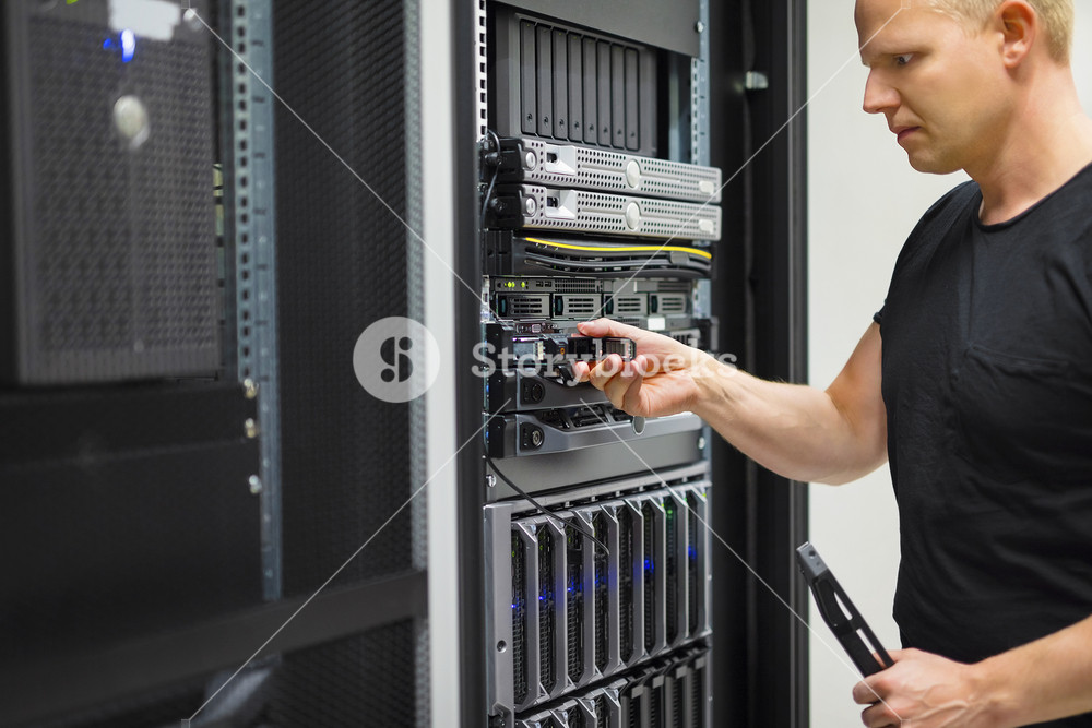 IT Engineer Installing Hard Drive In Rack Server