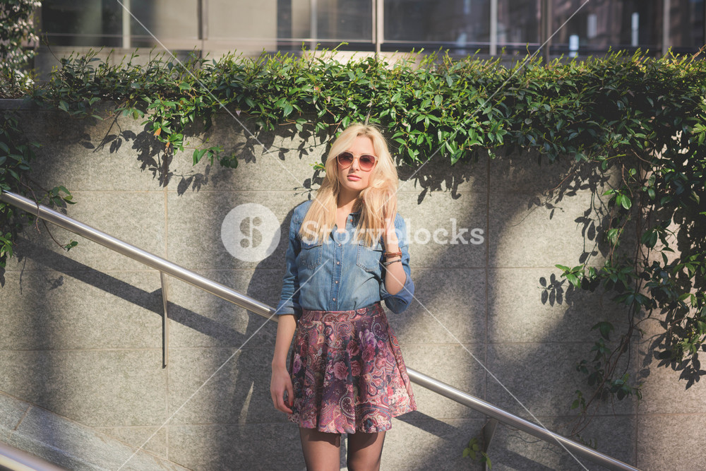 Knee figure of a young beautiful blonde caucasian girl posing in the city wearing a jeans shirt and a floral skirt looking in camera leaning on a wall - youth, freshness concept