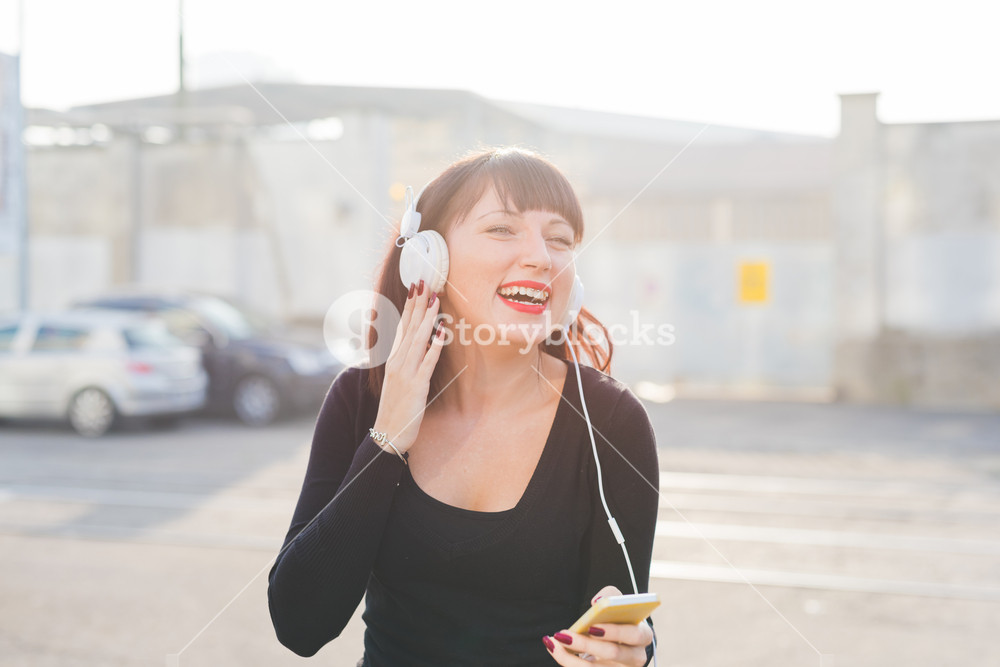 Knee figure of young beautiful eastern woman listening music with headphones and smart phone hand hold, eyes closed, laughing - music, technology, carefree concept