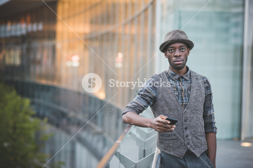 Knee figure of young handsome afro man holding a smartphone leaning on a handrail, looking in camera, copyspace on left - social network, communication, technology concept