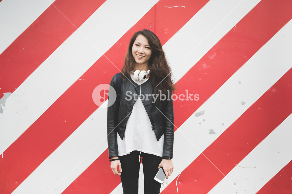 Knee figure of young handsome asiatic woman leaning against striped red and white wall, headphones around her neck and smartphone handhold, looking in camera smiling - happiness, carefree concept