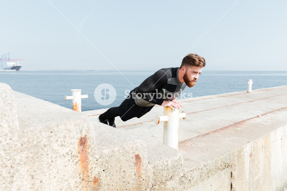 Man doing push ups near the sea. side view