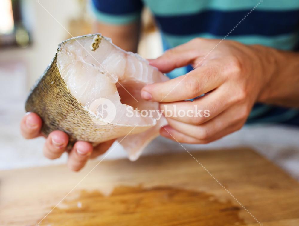 Man holding raw zander fish fillets on a wooden cutting board.