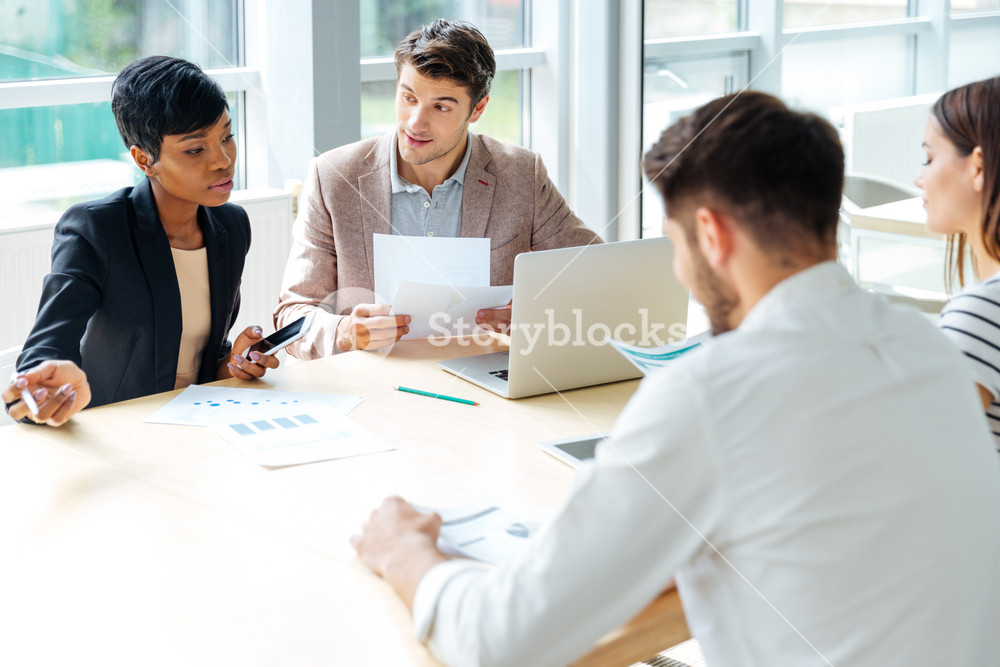 Multiethnic group of young businesspeople working together on business meeting in conference room