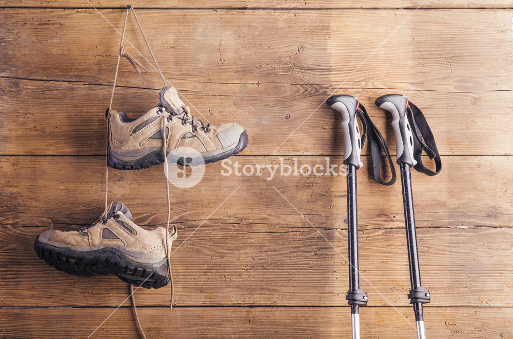 Nordic walking poles and hiking shoes hang on a wooden fence background