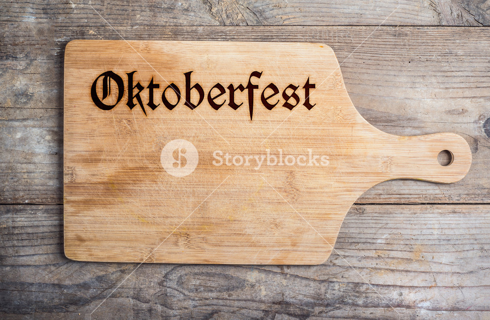 Octoberfest sign on cutting board, copy space, wooden background. Studio shot.
