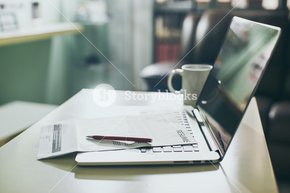 Office table with Laptop, tablet and resume information. Job search concept.