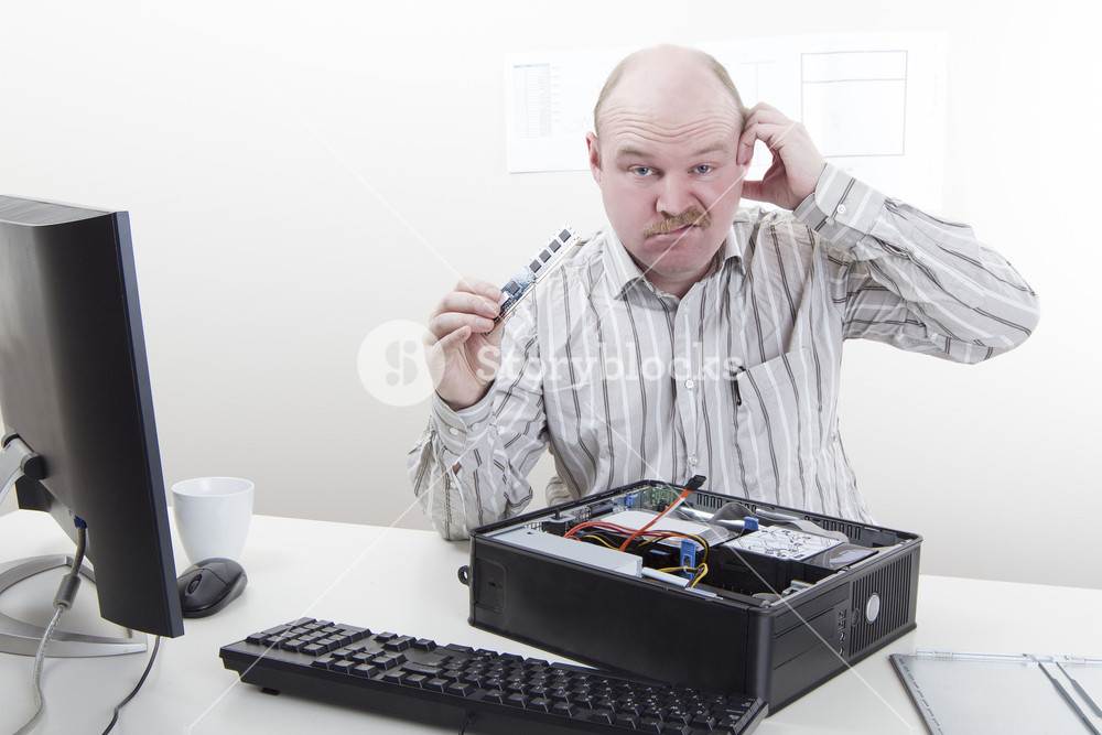 Office worker / businessman with computer / IT problems with a memory component in his hand.