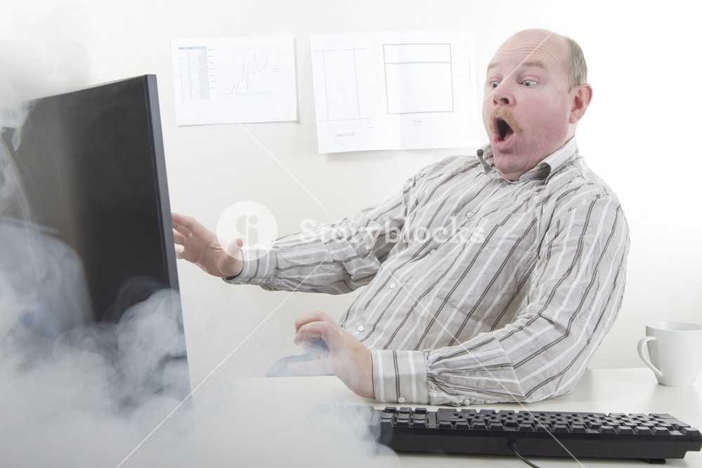 Office worker / businessman with computer problems or very fast internet / computer. Smoke coming from the computer screen.