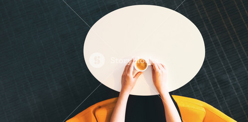Overhead view of person drinking an espresso in a modern cafe