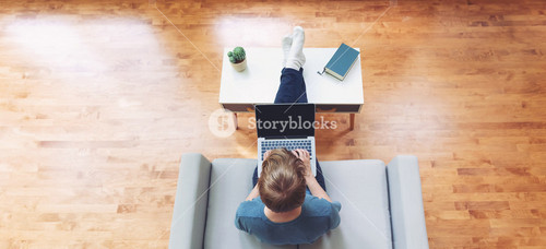 Overhead view of young blond person typing on laptop computer