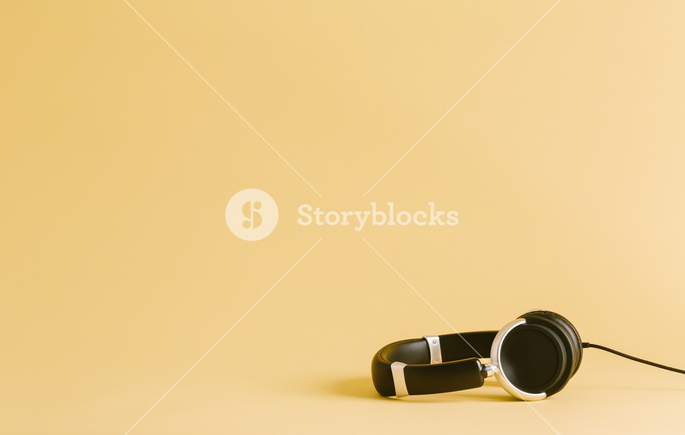 Pair of black headphones on a yellow background