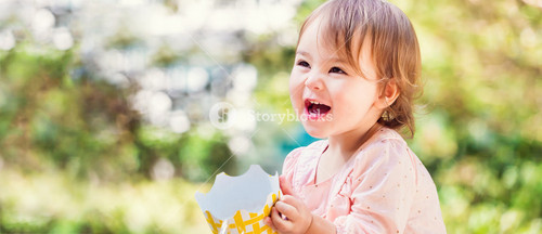Panoramic portrait of a happy toddler girl with a big smile outside