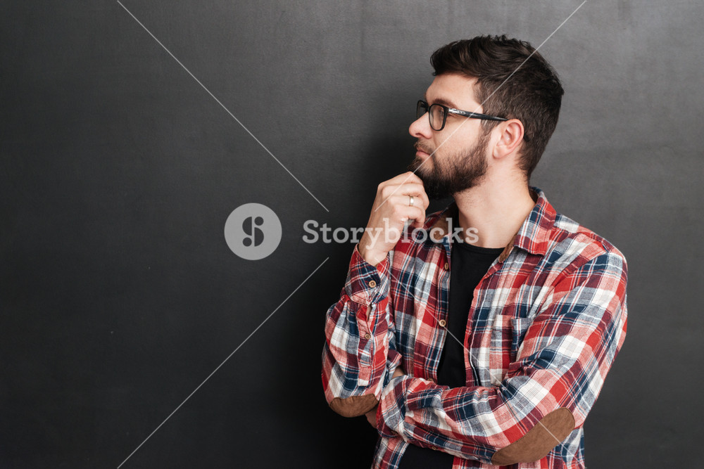 Pensive bearded young man in glasses and plaid shirt thinking and looking away over grey background