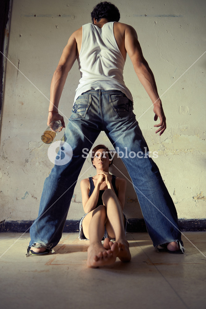 People, substance abuse and domestic violence. Drunk man standing with whiskey bottle and threatening his young wife at home