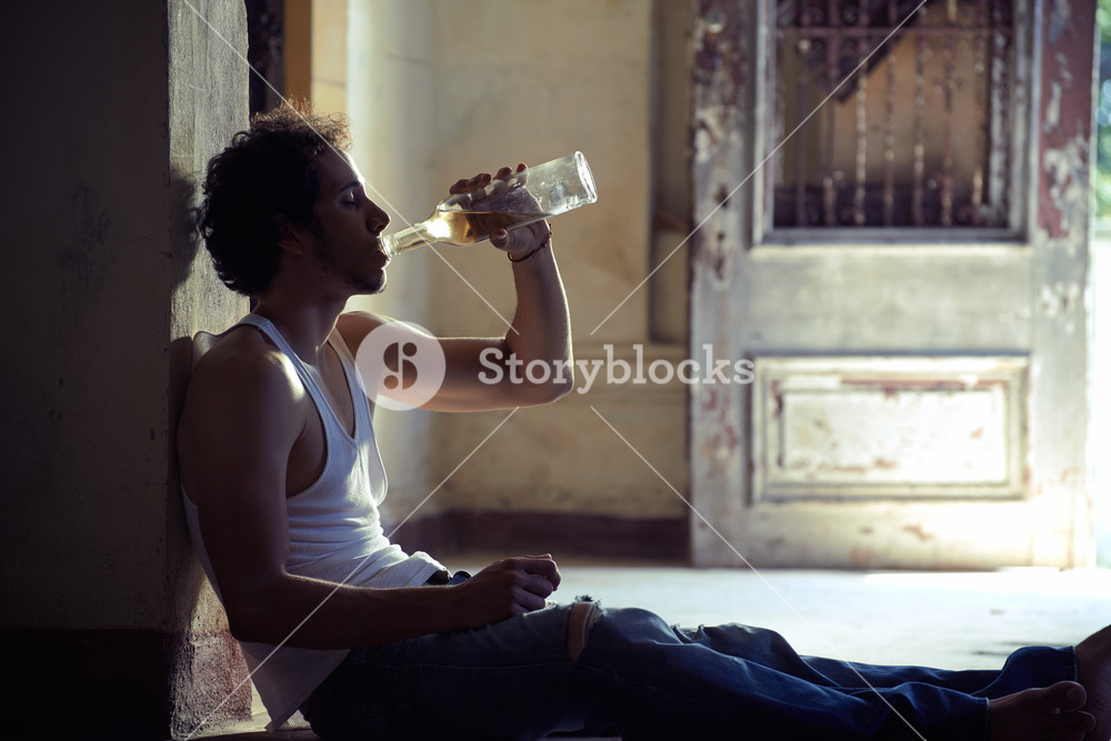 People, substance abuse and domestic violence. Portrait of young alcoholist drunk male drinking whisky at home