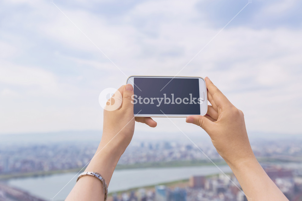 Person holding a cellphone on cityscape background