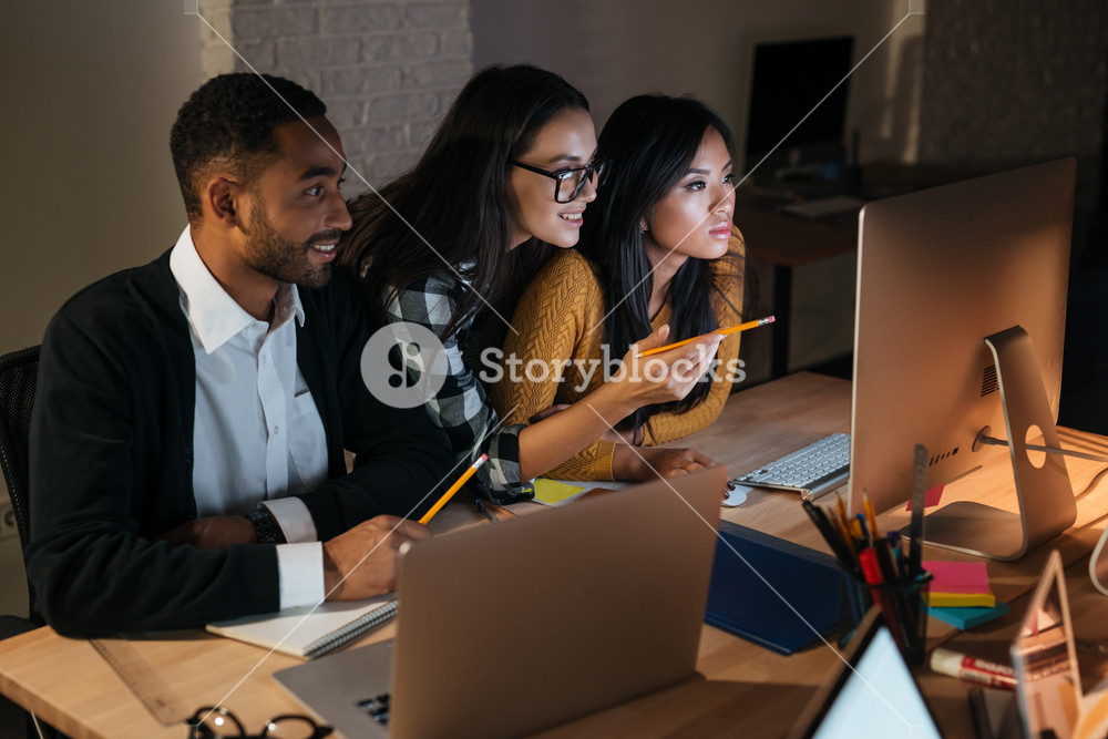 Photo of happy business people working late at night in their office with laptops and computers. Woman pointing with pencil to computer.