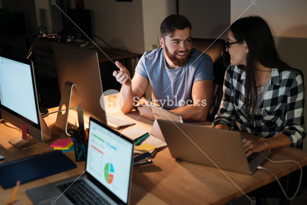 Photo of happy business people working late at night in their office with laptops and computers.