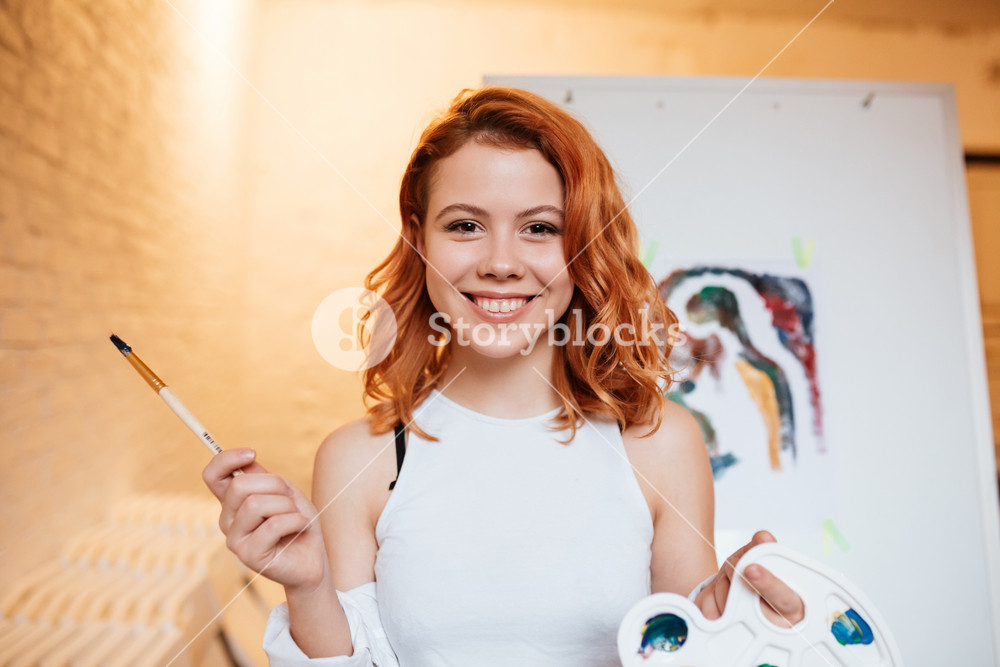 Photo of joyful lady painter with red hair standing over blank canvas in artist workshop. Look at camera while holding palette and paintbrush.