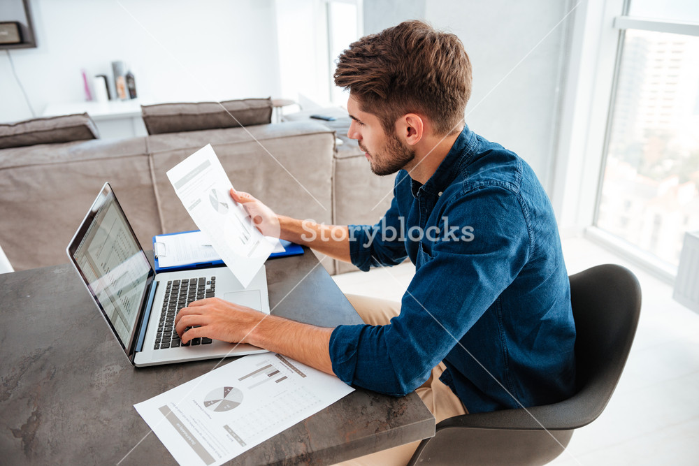 Photo of man typing on laptop and sitting at the table while looking at the papers of home finances.