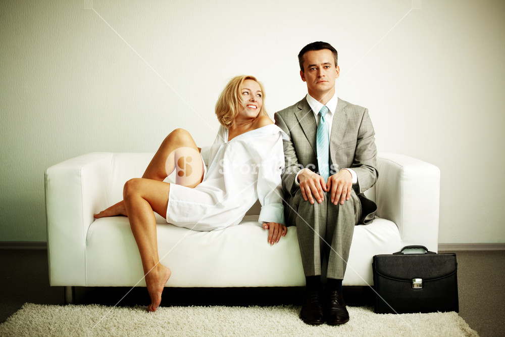 Photo of serious man sitting on sofa with happy seductive woman looking at him