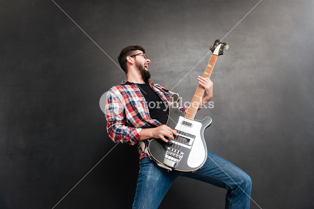 Photo of singing young man dressed in shirt in a cage standing over chalkboard while playing on the guitar. Music concept.