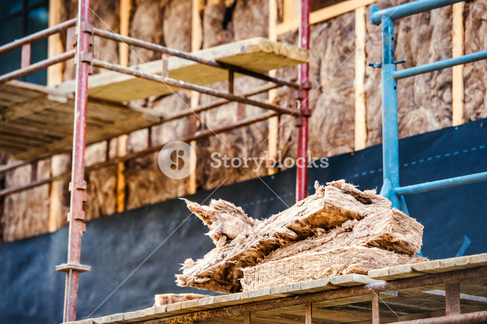 Pieces of glass thermal insulation wool on scaffold platform against house facade
