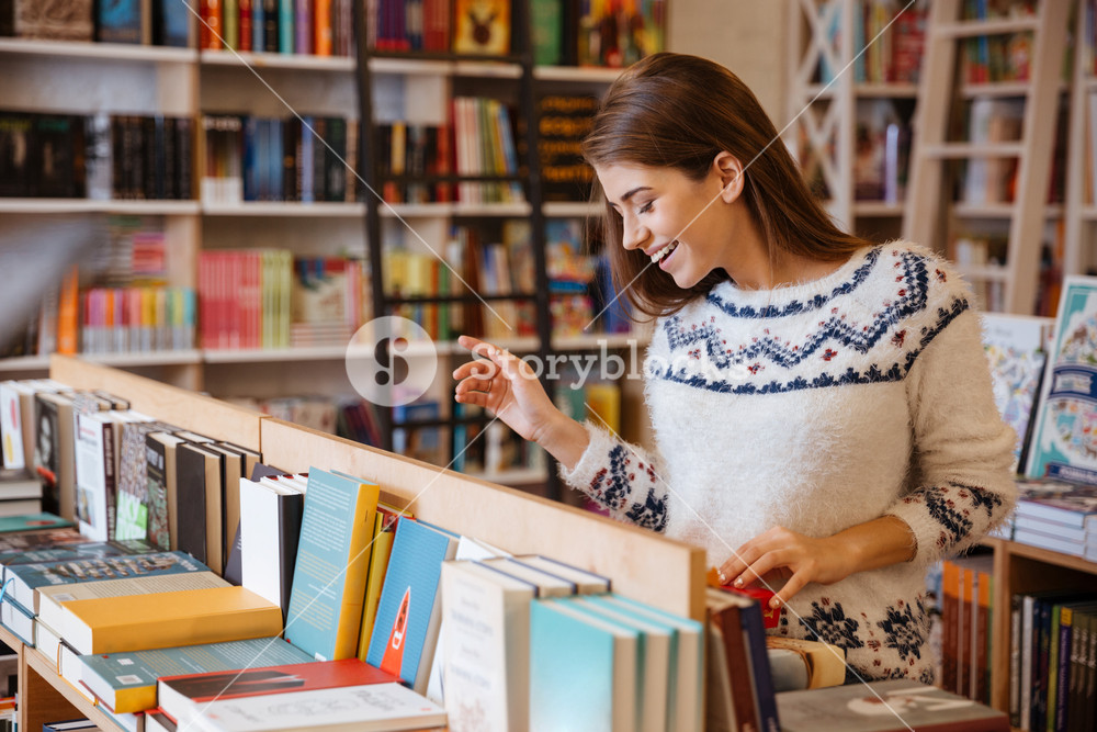 Portrait of a beautiful brunette woman looking for a book in store